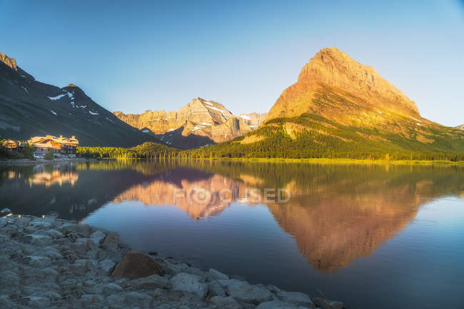 Beautiful rocky mountains and green trees reflected in water at sunny day — стоковое фото