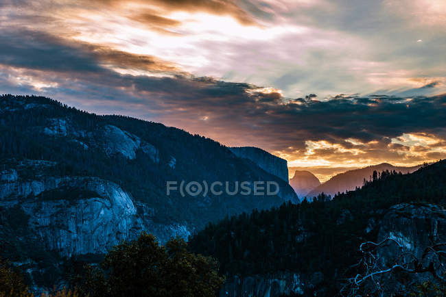Beautiful landscape with rocky mountains and green vegetation during sunset - foto de stock