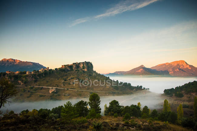 Amazing landscape with scenic mountains in fog and clear sky at morning — Photo de stock
