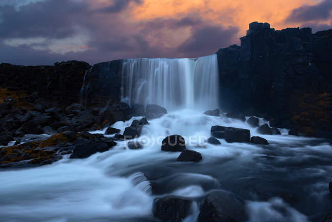 Amazing landscape with majestic waterfall and rocks at sunset — Fotografia de Stock