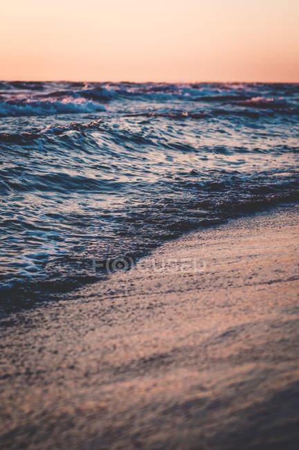 Beautiful ocean wave over sand at sunset, selective focus — Fotografia de Stock