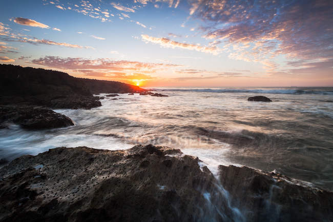 Scenic ocean waves on rocky shore at sunset — стокове фото