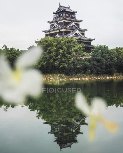 Reflection of traditional asian temple in calm lake, selective focus — Stockfoto
