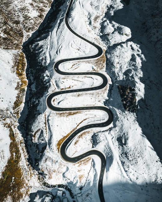 Vista aerea della strada tortuosa in montagne panoramiche innevate — Foto stock