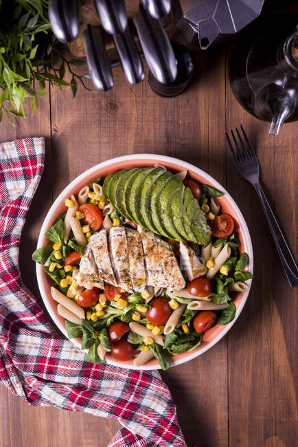 Top view of bowl with vegetables, pasta and meat on wooden table — Stockfoto