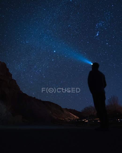 Silhouette di persona con torcia elettrica guardando la via lattiginosa sul cielo — Foto stock