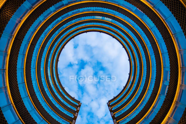 Vista in basso dell'edificio rotondo a spirale e del cielo blu con nuvole — Foto stock