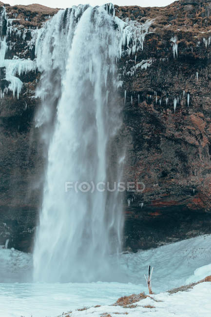 Scenic snow-covered waterfall during daytime, time lapse photography — Stockfoto