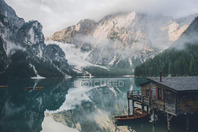 Holzhaus, Boote und schneebedeckte Berge im ruhigen See — Stockfoto