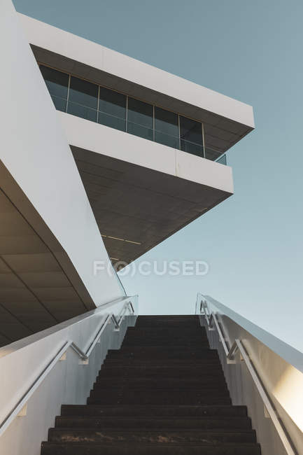 Low angle view of stairs of modern white building and clear blue sky — стокове фото