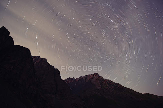 Rocky mountains against majestic starry sky at night — Photo de stock