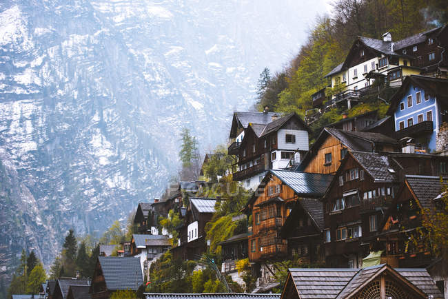 Low angle view of steep-slope homes by beautiful mountain peak — Stock Photo