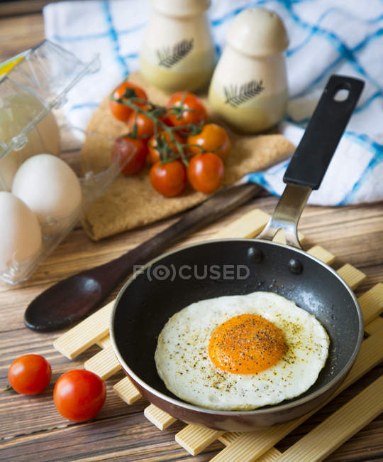Close-up view of egg with spices cooking on frying pan and tomatoes on wooden table — Stockfoto