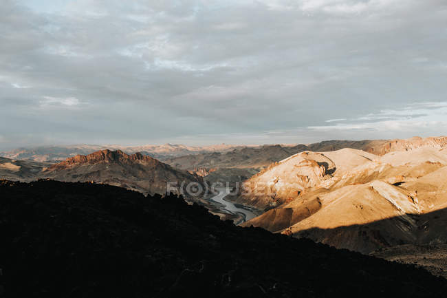 Amazing landscape with scenic mountains and river under cloudy sky — Foto stock