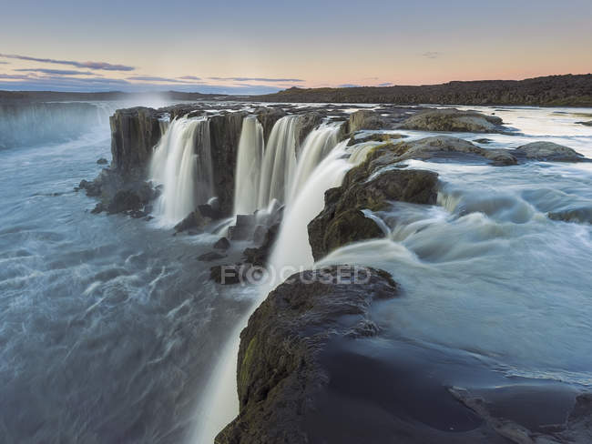 Aerial view of majestic waterfall at scenic sunset - foto de stock