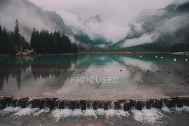 Water flowing from lake and beautiful mountains in clouds — Stockfoto