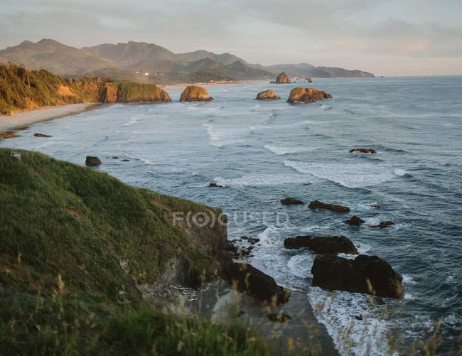 Beautiful natural view with hills, cliffs and wavy sea at sunset - foto de stock