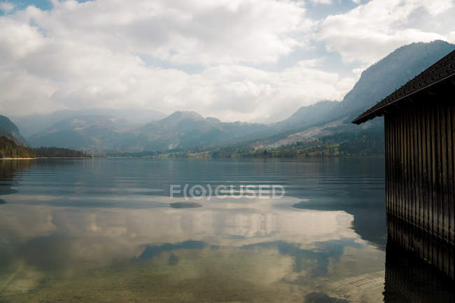 Scenic mountains and cloudy sky reflected in calm water — Foto stock