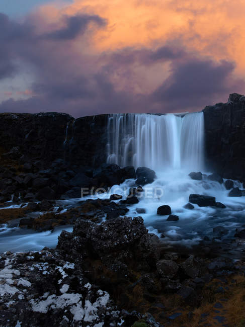 Beautiful landscape with scenic waterfall and rocks at sunset — Fotografia de Stock