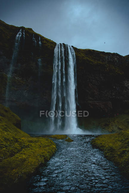 Low angle view of beautiful waterfall under grey sky — стокове фото