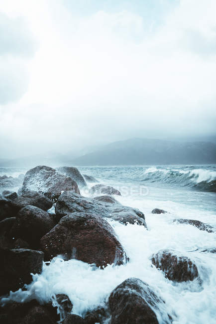 Majestic seascape with waves crashing into rocks at cloudy day — стокове фото