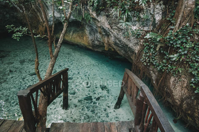 High angle view of wooden railings and transparent water near rocks — стоковое фото