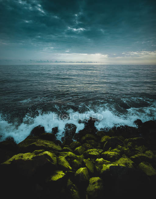 Amazing seascape with waves and green rocks under cloudy sky - foto de stock