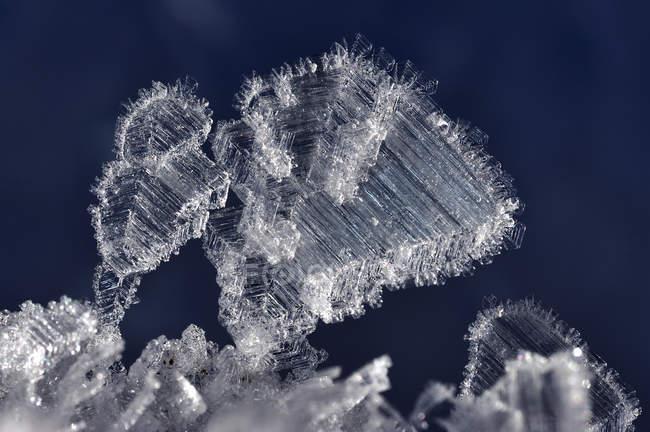 Vista cercana de cristales de hielo congelados blancos en fondo azul - foto de stock