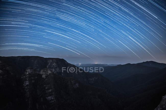 Céu nocturno surpreendente com as estrelas acima das montanhas cénicas — Fotografia de Stock