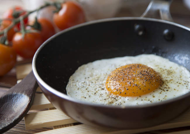 Close-up view of egg with spices cooking on frying pan — Stockfoto