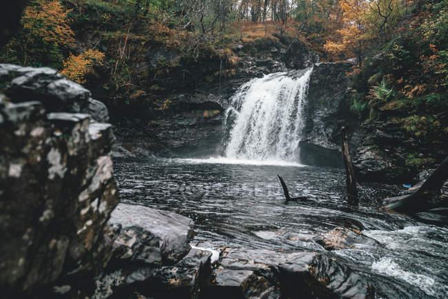 Wide angle view of beautiful waterfall, rocks and trees — Fotografia de Stock