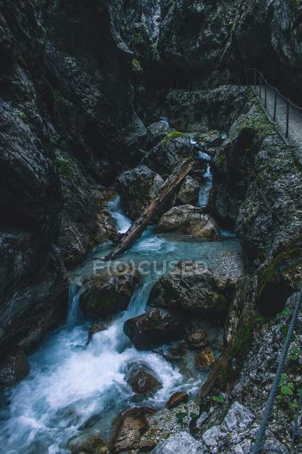 High angle view of scenic waterfall, rocks and wood log into water - foto de stock