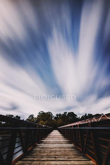 Empty wooden bridge, green trees and amazing blue sky with clouds — Photo de stock