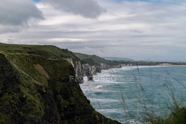 Vista natural bonita dos montes cobertos com a vegetação verde e o mar cénico no dia nebuloso — Fotografia de Stock