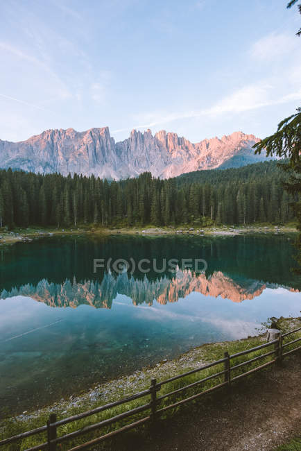 Beautiful landscape with rocky mountains and green forest reflected in calm lake - foto de stock