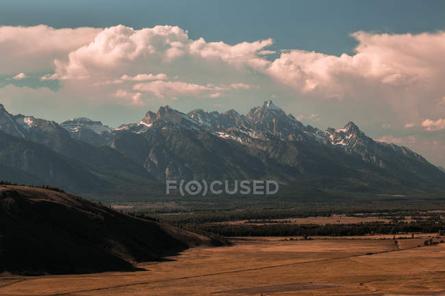 Beautiful landscape with reddish sand in valley and scenic rocky mountains - foto de stock