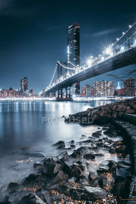 Low angle view of illuminated bridge and modern buildings reflected in river at night — стоковое фото