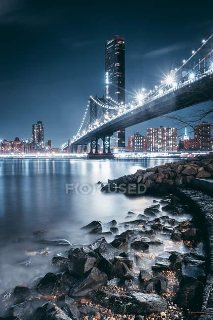 Niedrigwinkelansicht der beleuchteten Brücke und moderner Gebäude, die sich nachts im Fluss spiegeln — Stockfoto