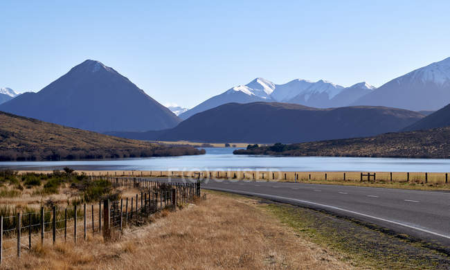 Beautiful landscape with lake, valley, mountains and road at sunny day — Fotografia de Stock