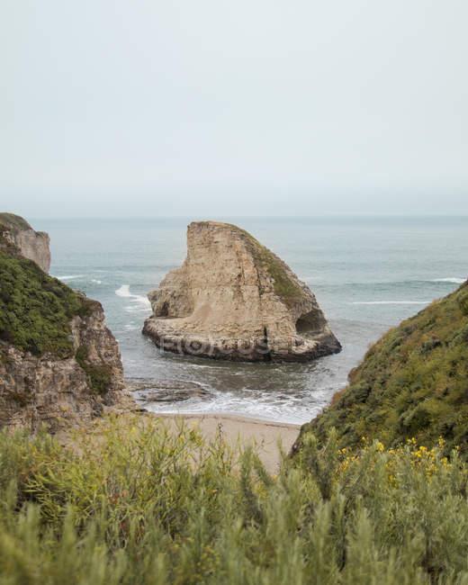 Vista natural bonita do penhasco no mar ondulado no dia nebuloso — Fotografia de Stock