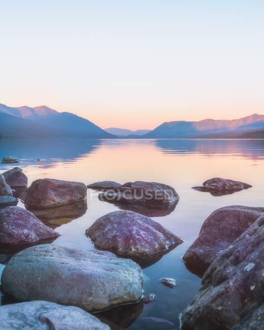 Vista cénico das rochas na água calma e nas montanhas bonitas no nascer do sol — Fotografia de Stock