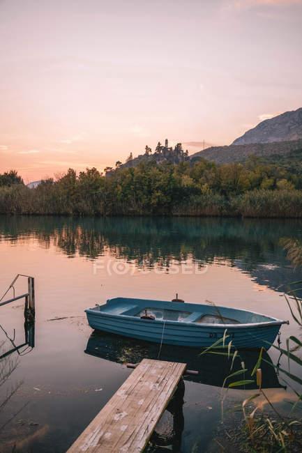 Barco de encontro ao cais de madeira minúsculo e ao lago calmo no nascer do sol — Fotografia de Stock