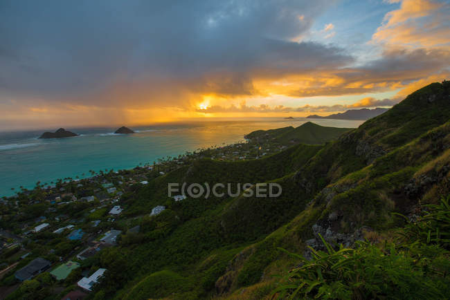 Beautiful mountains covered with green vegetation, small village on coast and amazing seascape at sunset — Fotografia de Stock