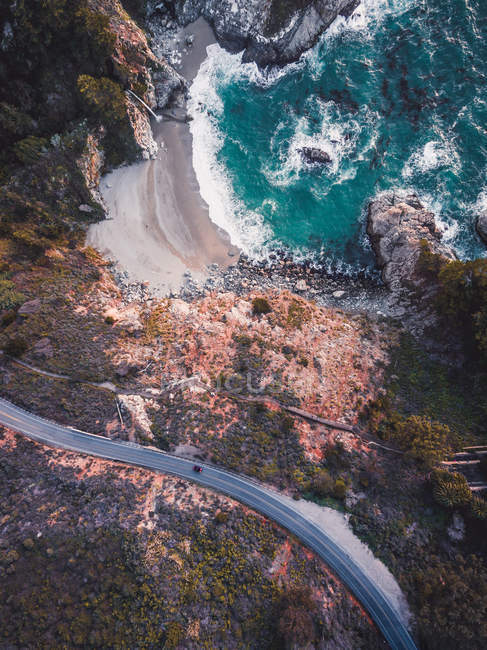 Aerial view of beautiful wavy sea, rocky mountains and road — стокове фото