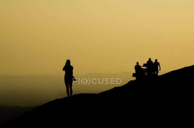 Silhouettes of friends standing on mountain slope in the evening — стокове фото