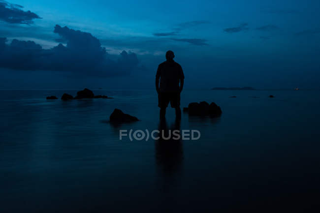 Silhouette of man standing on body of water against dark blue sky — Photo de stock