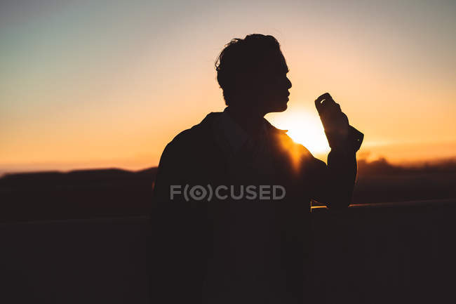 Silhouette of man standing outdoor against beautiful sunset sky — Photo de stock