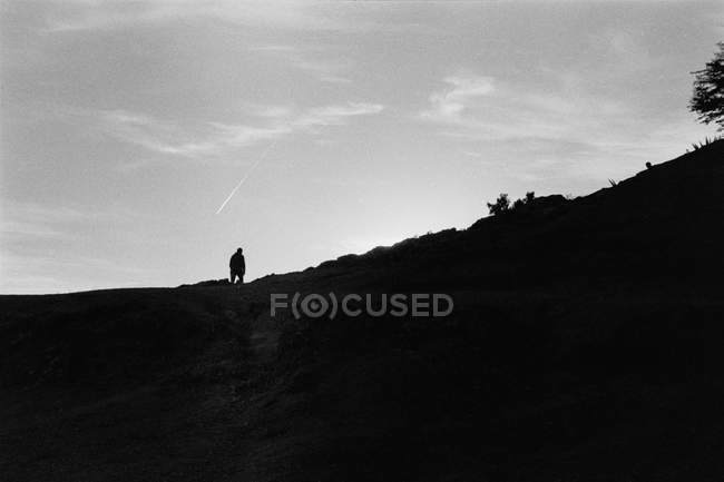 Silhouette of person walking on mountain against grey sky — Photo de stock