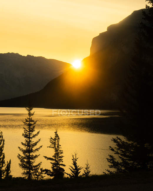 Silhouettes of mountains beside body of water during scenic sunset — Foto stock