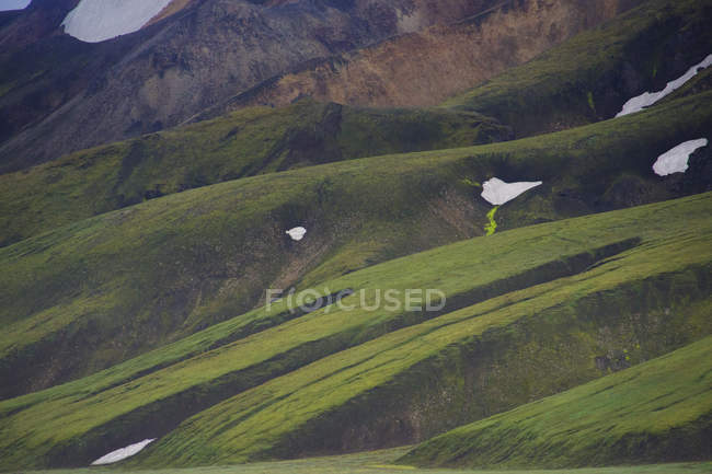 Scenic view of slope area with snow and green grass — Photo de stock
